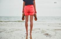 Person Standing In Sea Shore Holding Shoes In Hands